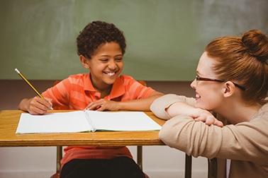 Teacher assisting boy with homework in classroom