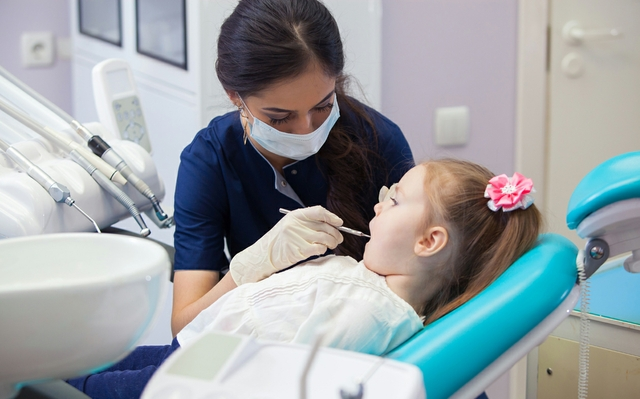 female dentist in mask treats teeth little girl
