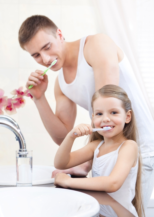 Little girl cleans teeth with her father