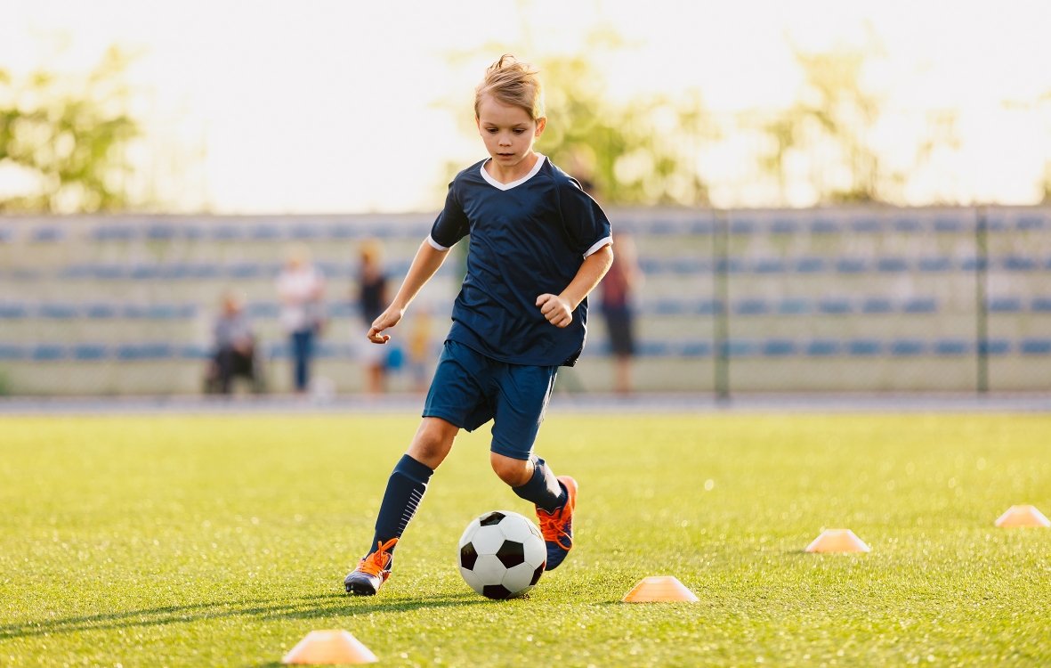 Young boy in blue soccer jersey uniform running after ball on tr