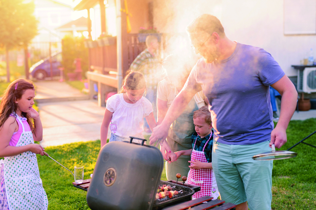 Proud happy father making barbeque for his family in backyard. S