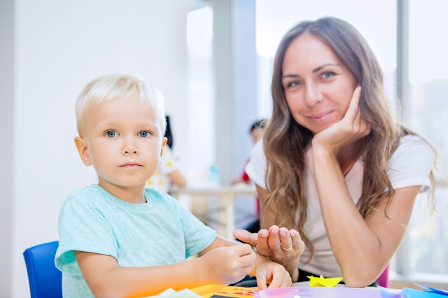 Little boy and teacher gluing trinkets in kindergarten